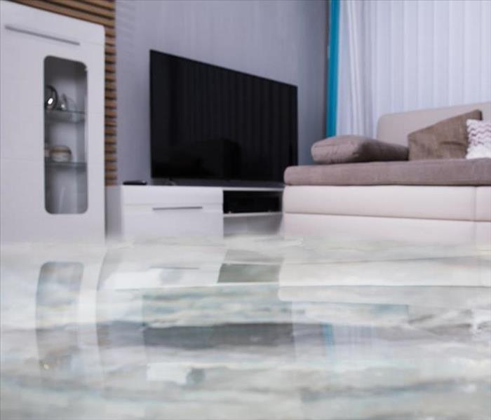 Water floods the living room of contemporary style home with white walls, tv, couch, curtains