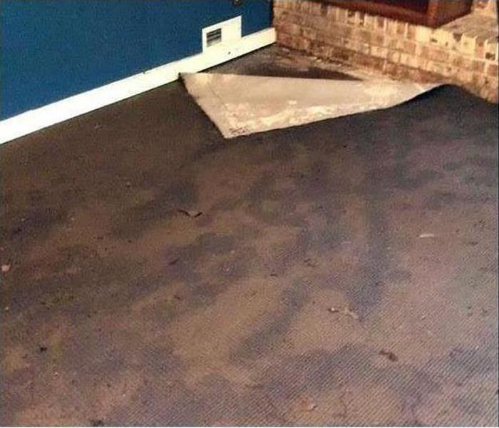 A part of the carpet pulled up in this home after water damage soaked it