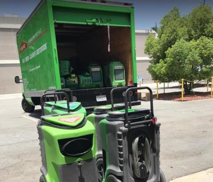SERVPRO truck open showing restoration equipment in truck and on ground
